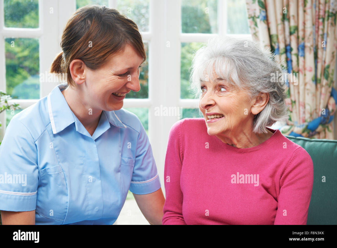 Senior Woman Chatting With Carer - Stock Image