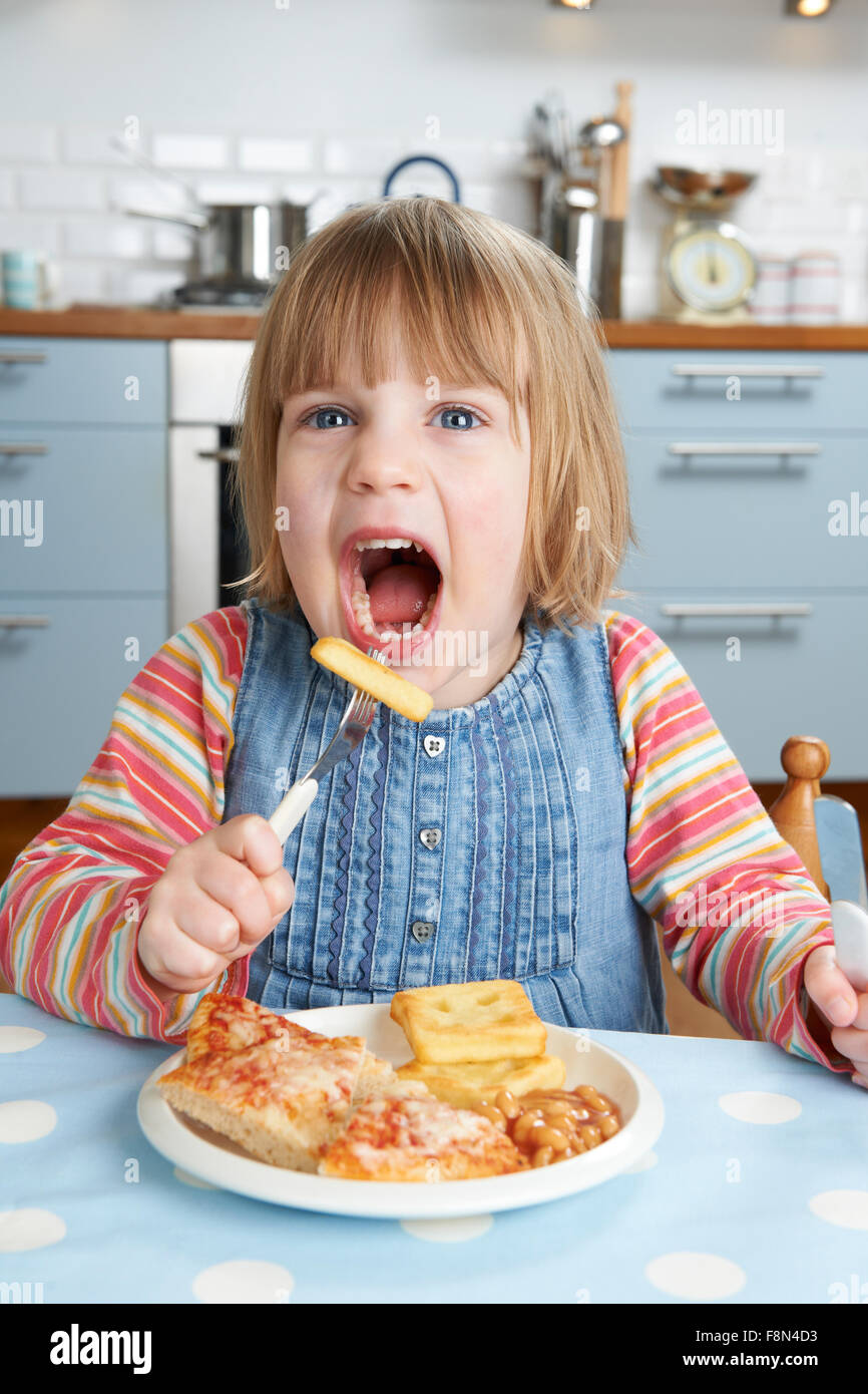 Young Girl Enjoying Unhealthy Lunch - Stock Image