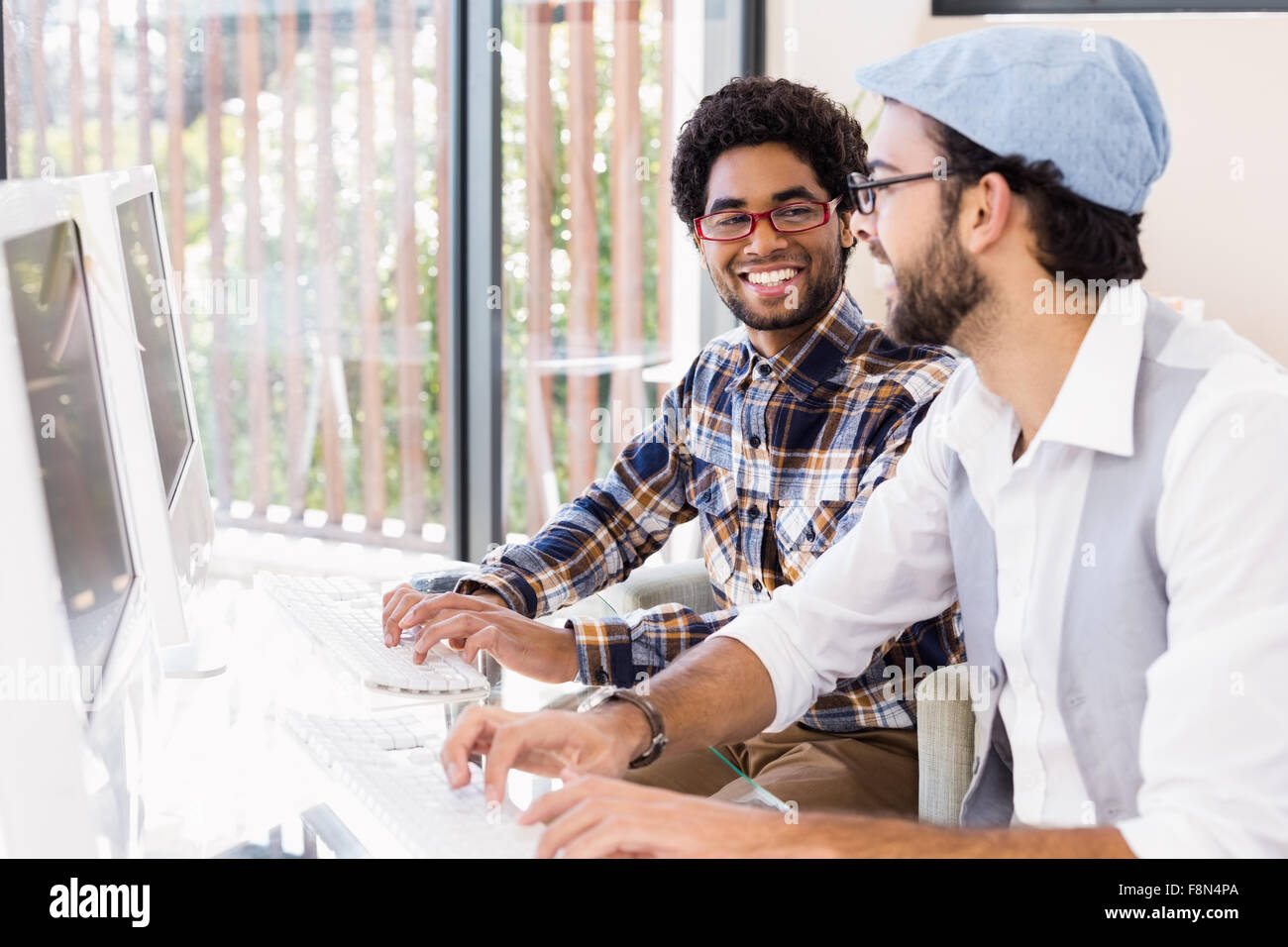 Smiling gay couple talking while working on computers - Stock Image