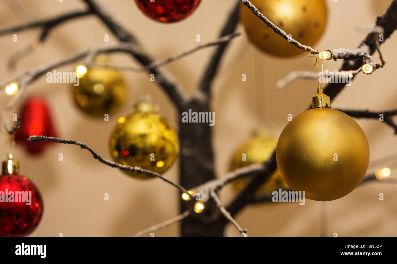 Christmas decorations hanging from contemporary christmas tree - Stock Image