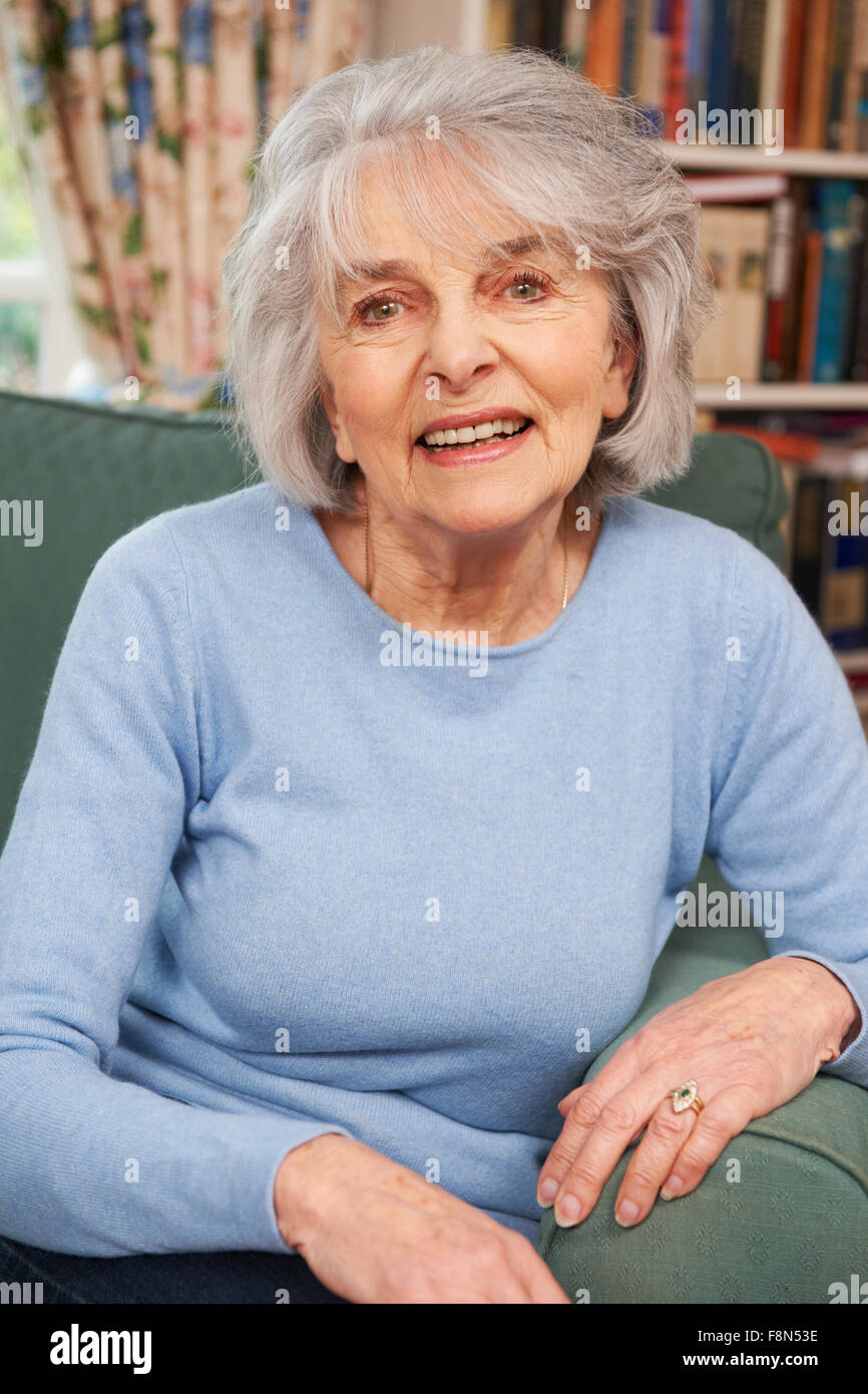 Portrait Of Smiling Senior Woman Sitting In Armchair - Stock Image