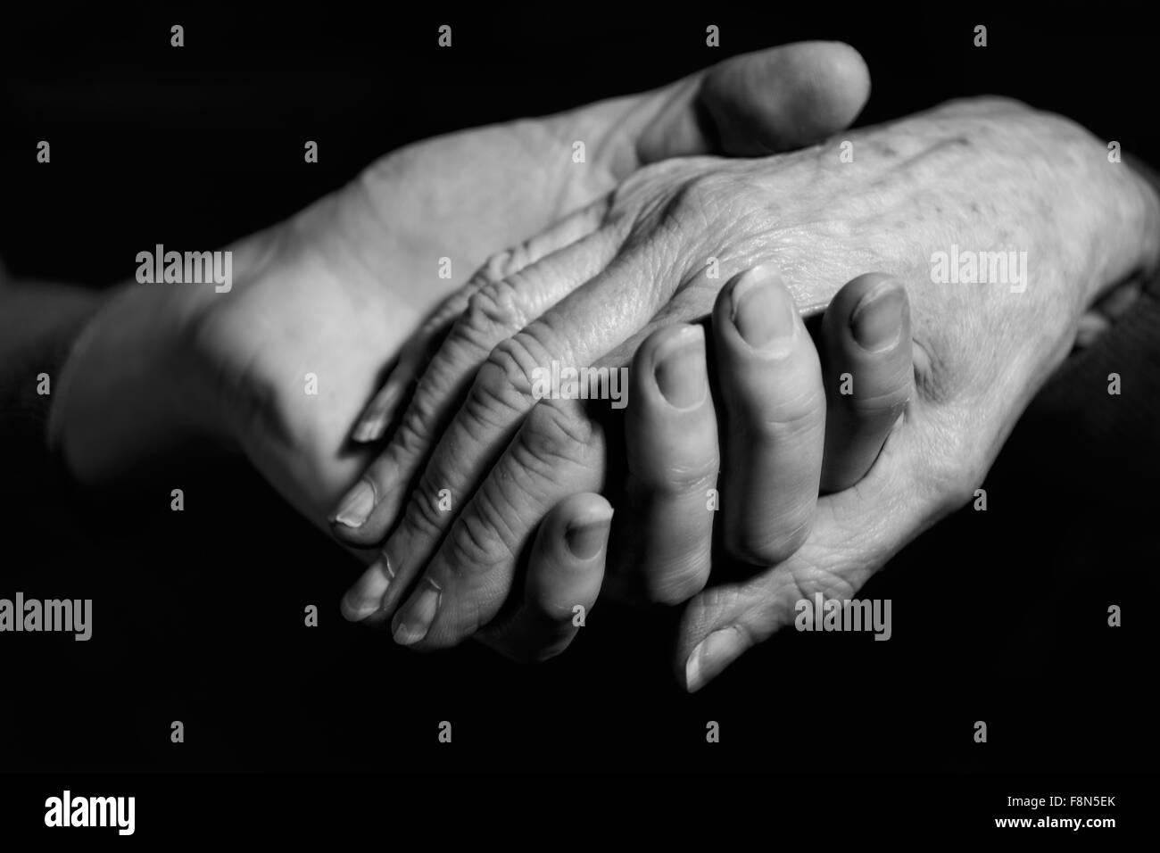 Monochrome Shot Of Young Woman Holding Older Woman's Hand - Stock Image