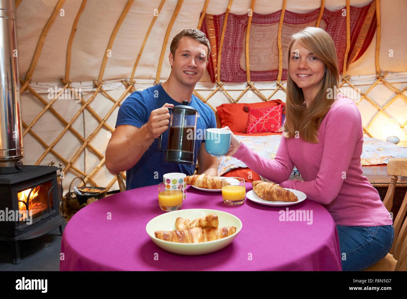 Couple Enjoying Holiday Camping In Traditional Yurt - Stock Image