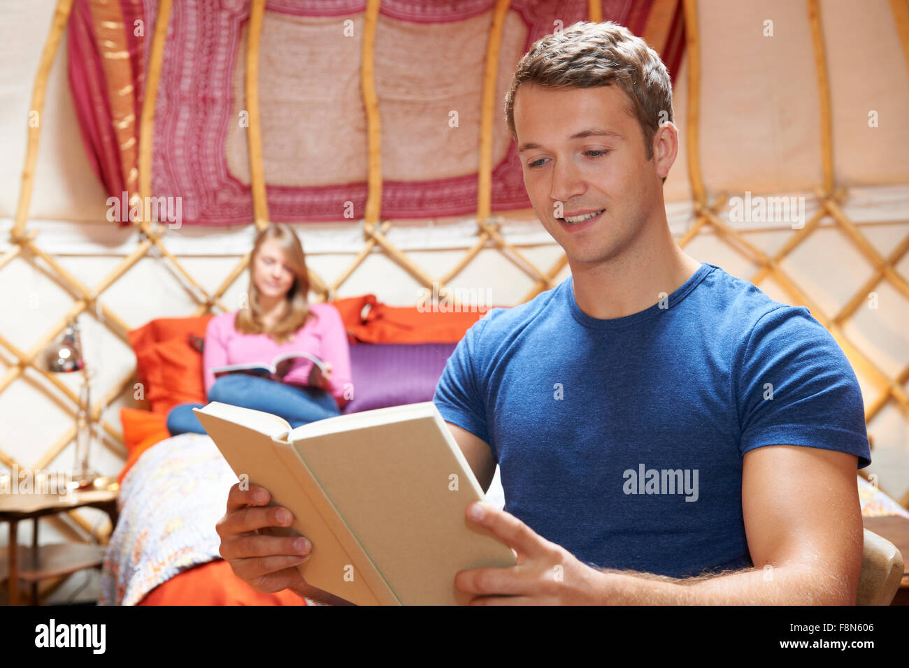 Couple Relaxing On Holiday In Yurt - Stock Image