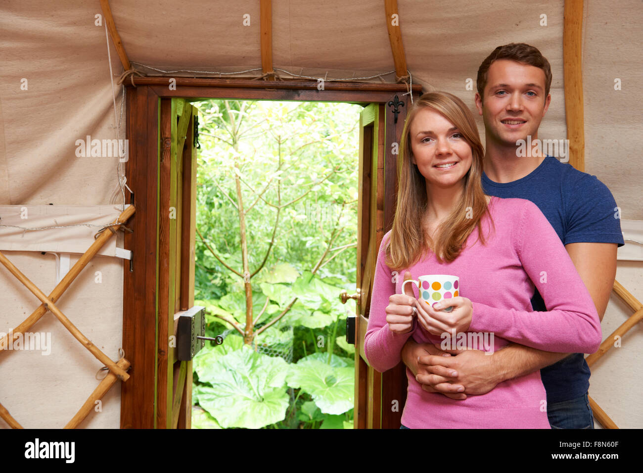 Couple Enjoying Luxury Camping Holiday In Yurt - Stock Image