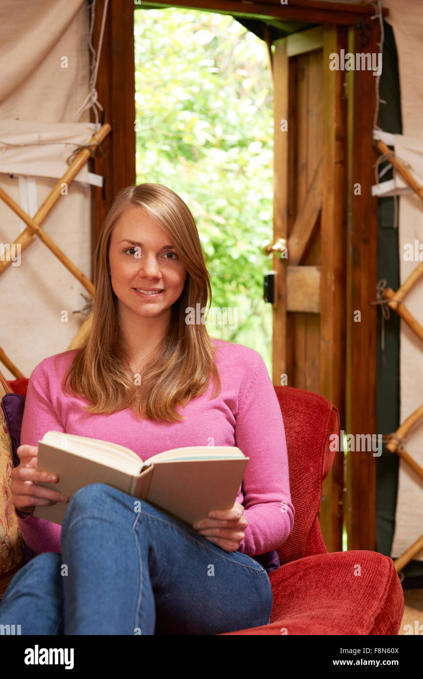 Woman Enjoying Luxury Camping Holiday In Yurt - Stock Image