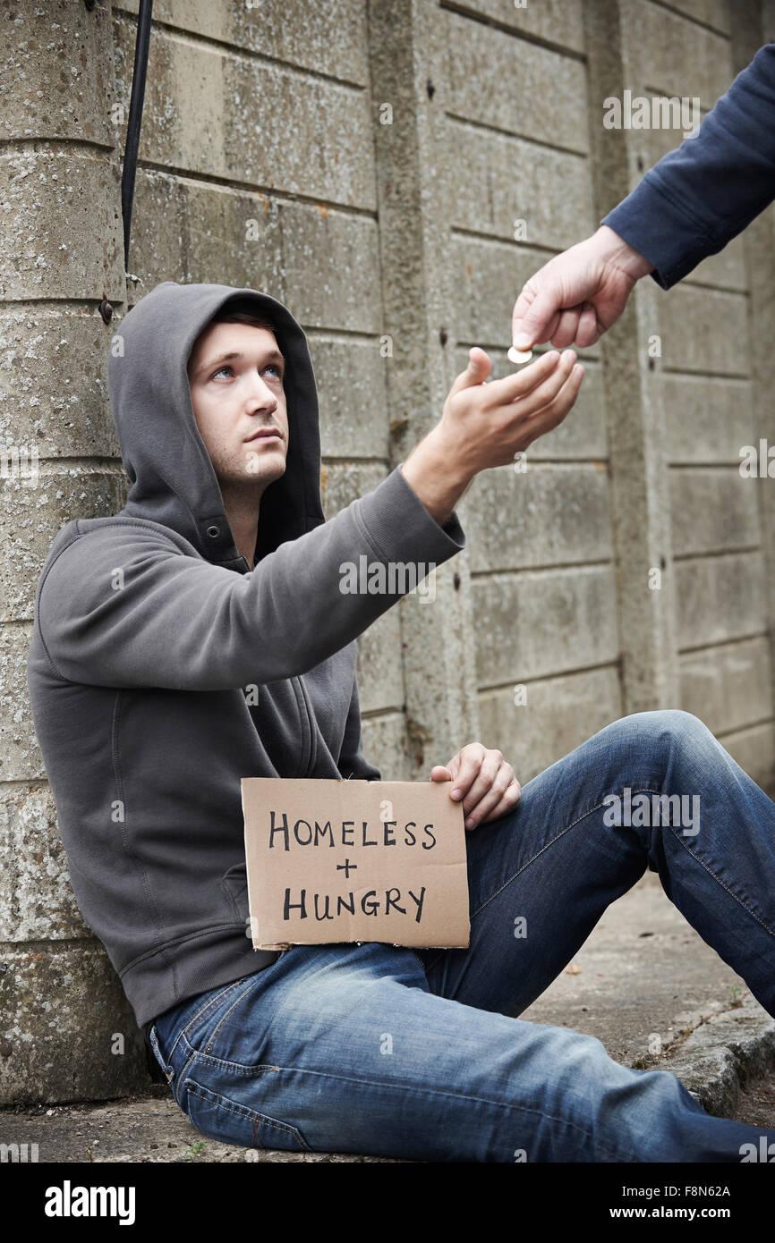 Man Giving Money To Beggar On Street - Stock Image