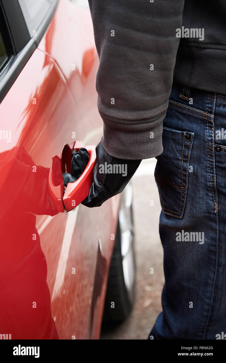 Car Thief Trying Door Handle To See If Vehicle Is Unlocked - Stock Image