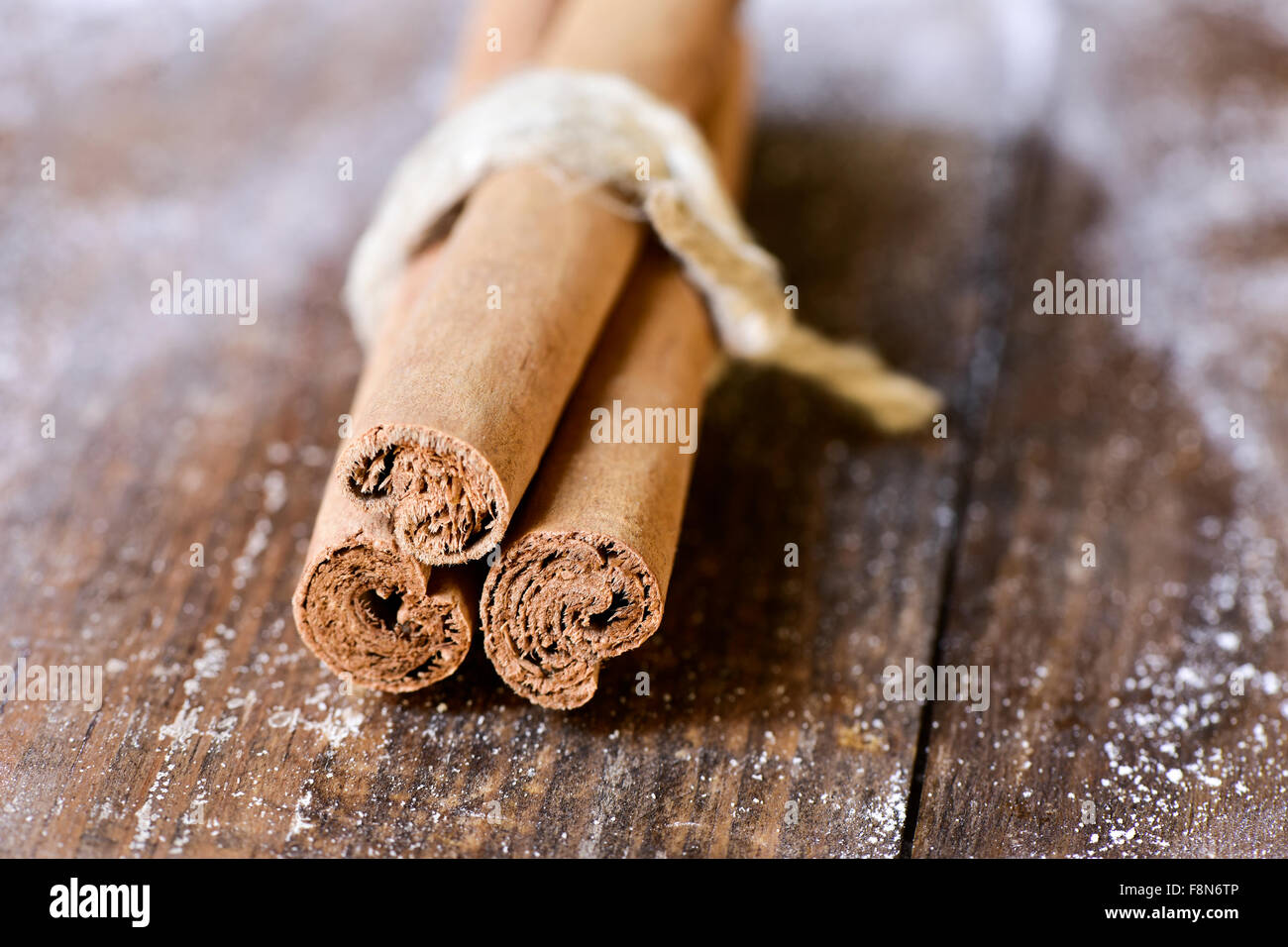 some cinnamon quills tied with a string on a rustic wooden surface Stock Photo