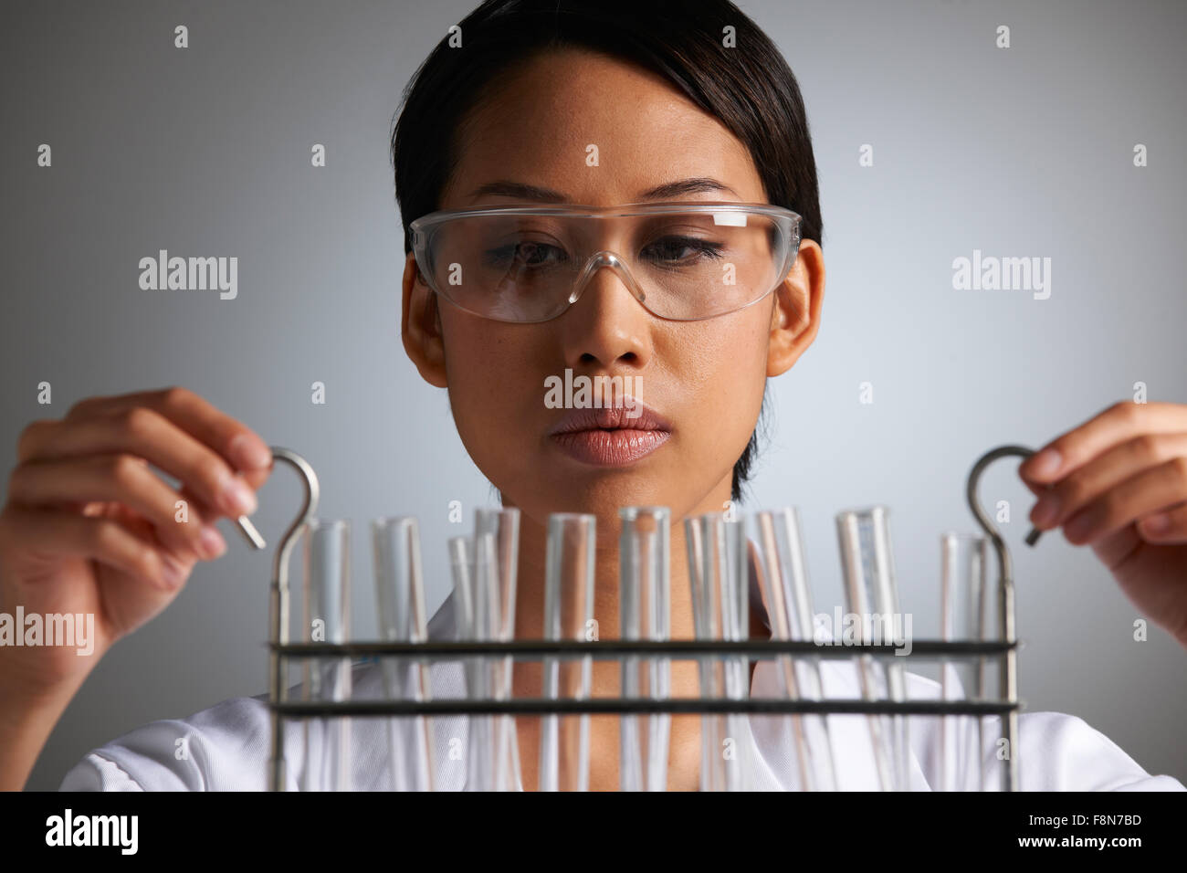 Female Scientist Examines Test Tubes - Stock Image