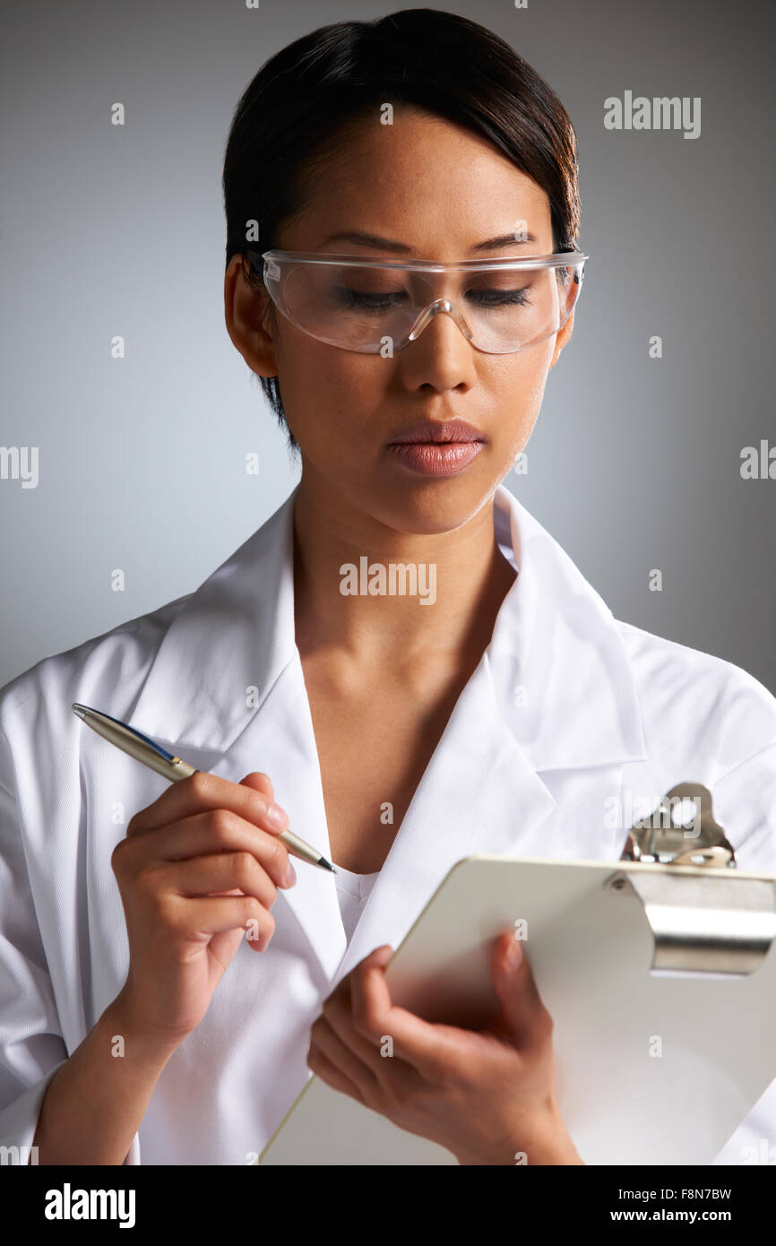 Female Scientist Writing On Clipboard - Stock Image