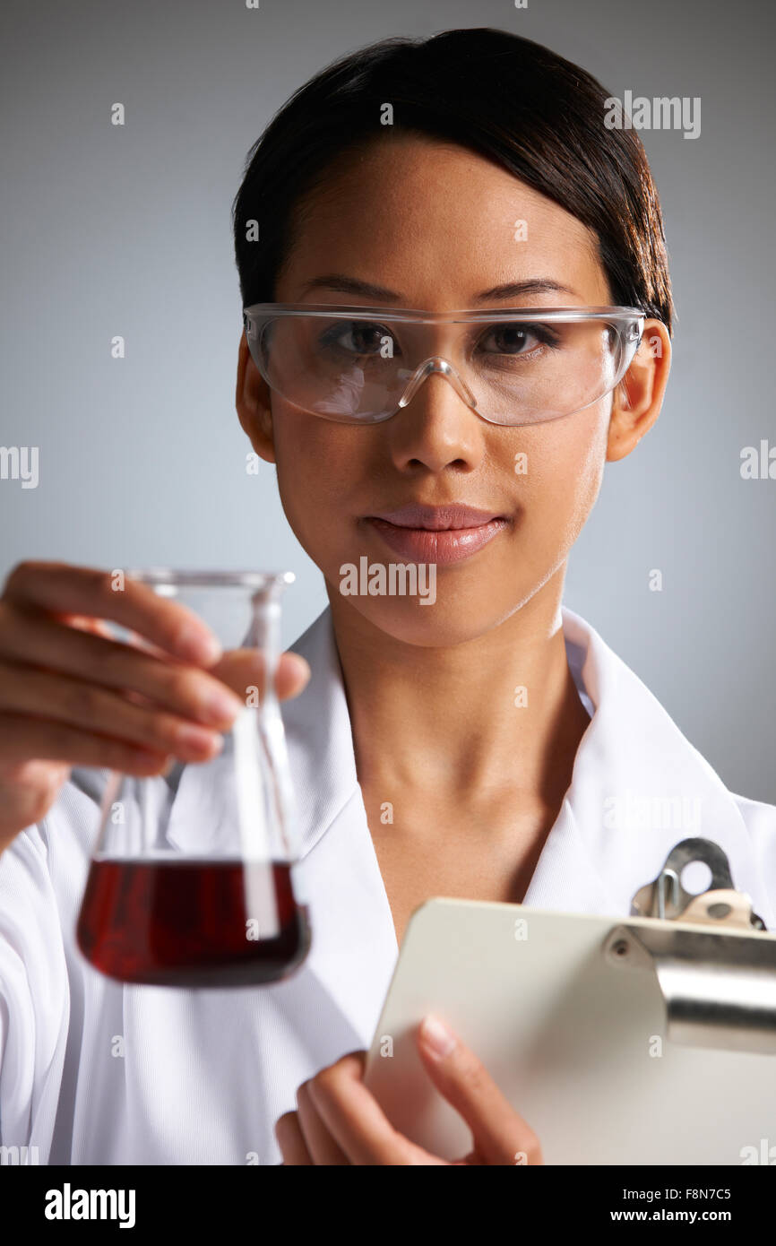 Scientist With Clipboard Examining Beaker - Stock Image