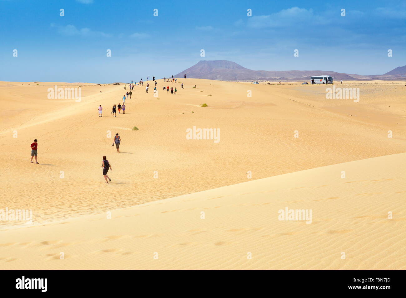 Fuerteventura Island, tourists walking on sand dunes in Parque Natural de Corralejo, Spain, Canary Islands - Stock Image