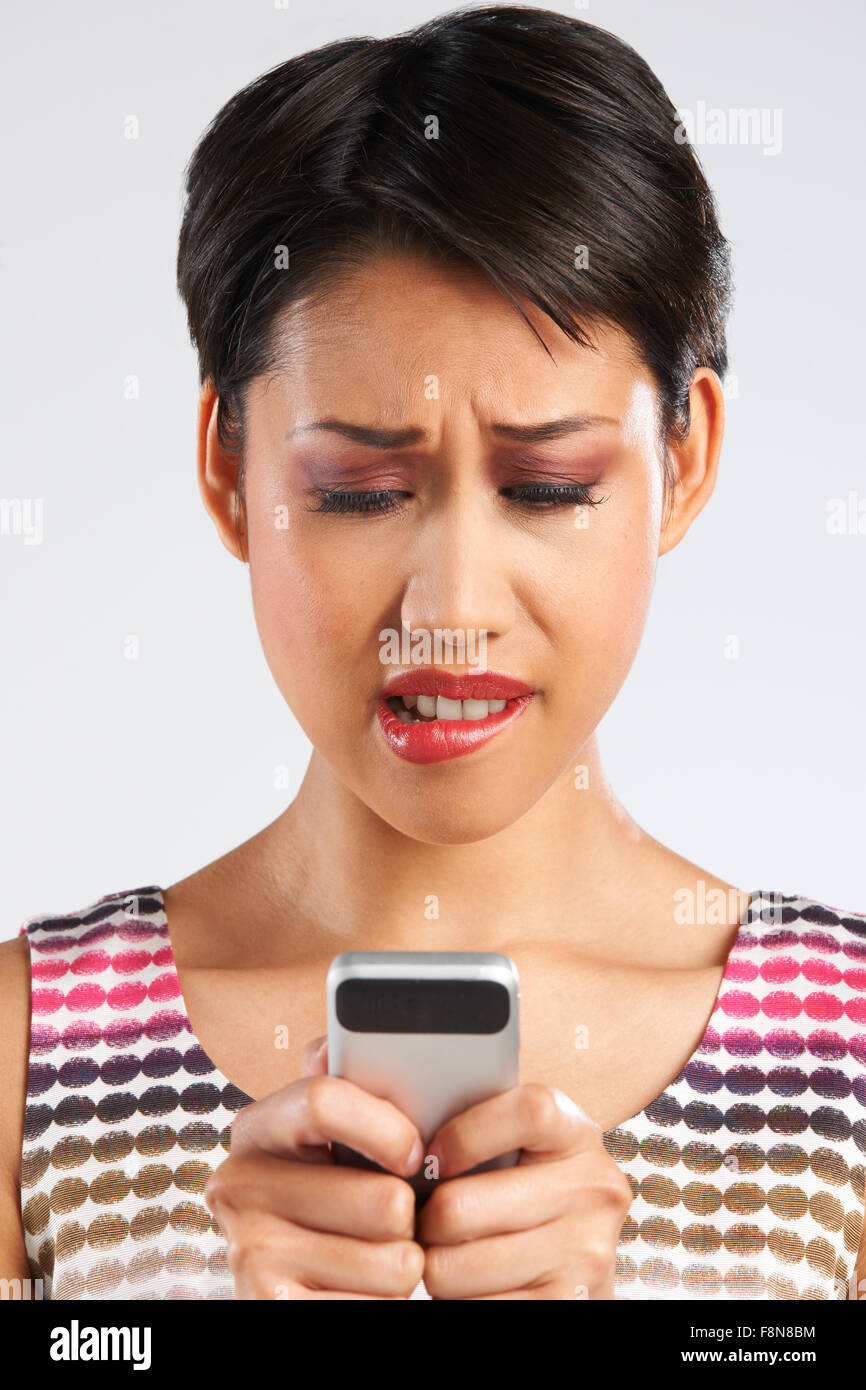 Young Woman Reading Text Message With Anxious Expression - Stock Image