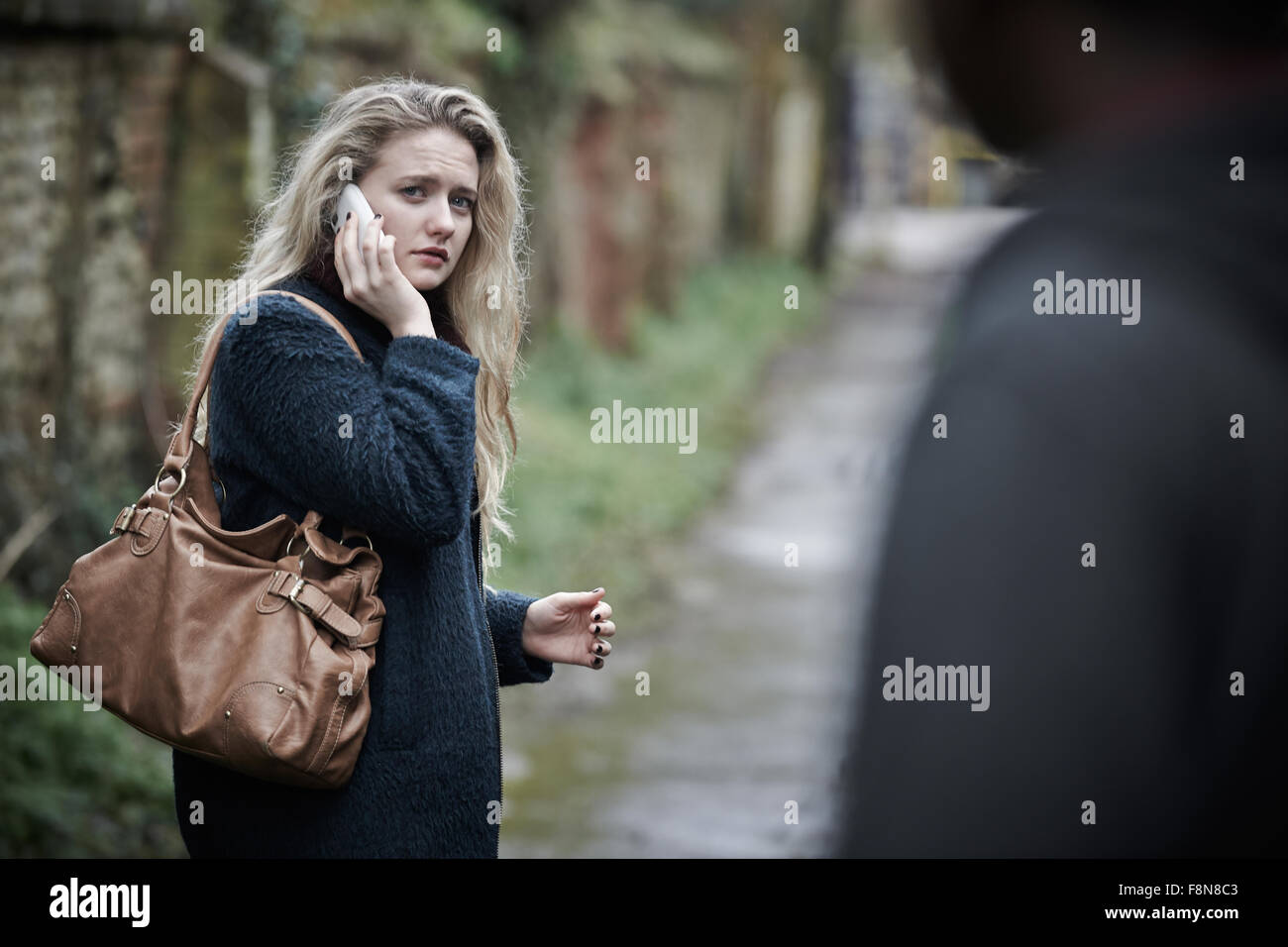 Young Woman Feeling Threatened As She Walks Home - Stock Image
