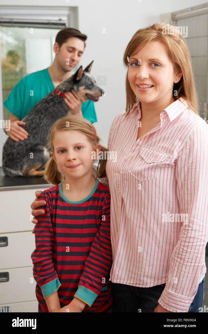 Mother And Daughter Taking Dog For Examination At Vets - Stock Image