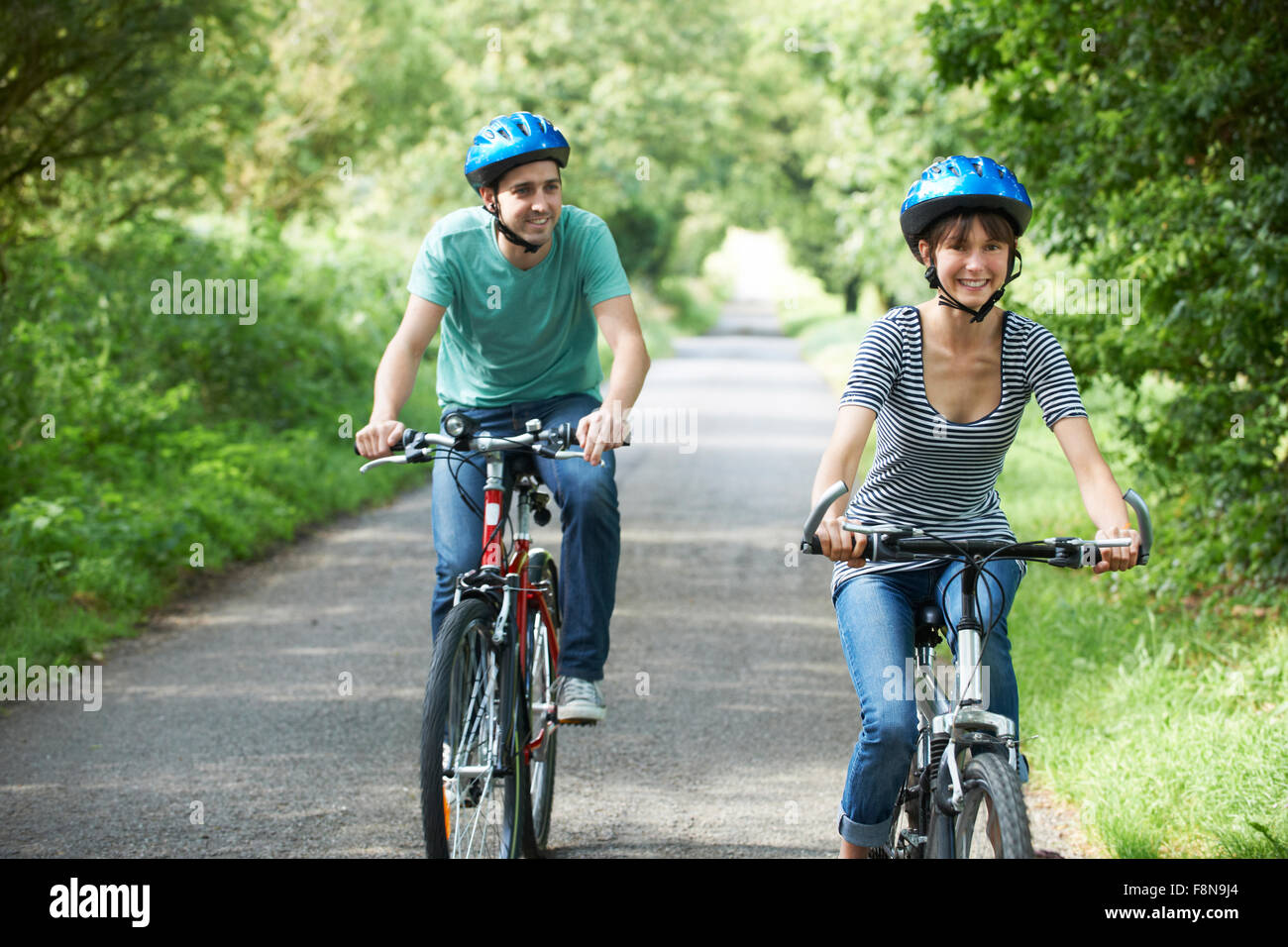 Young Couple Cycling Along Country Road - Stock Image