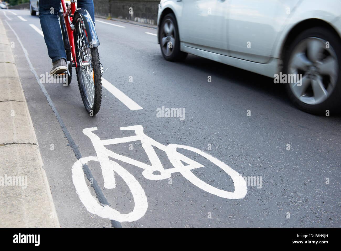 Man On Bike Using Cycle Lane As Traffic Speeds Past - Stock Image