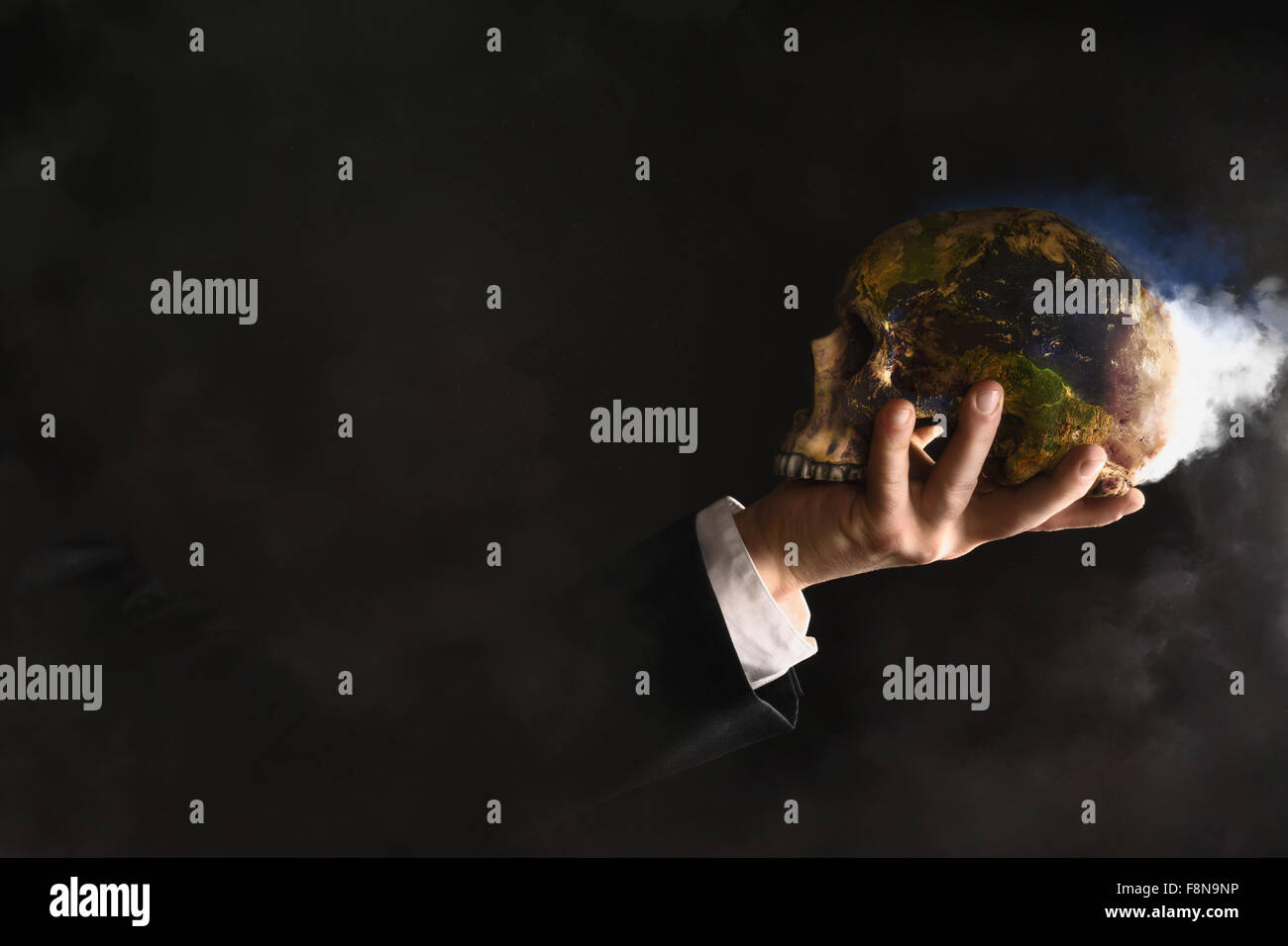 Businessman holding a burning globe while they changed into a skull - Stock Image