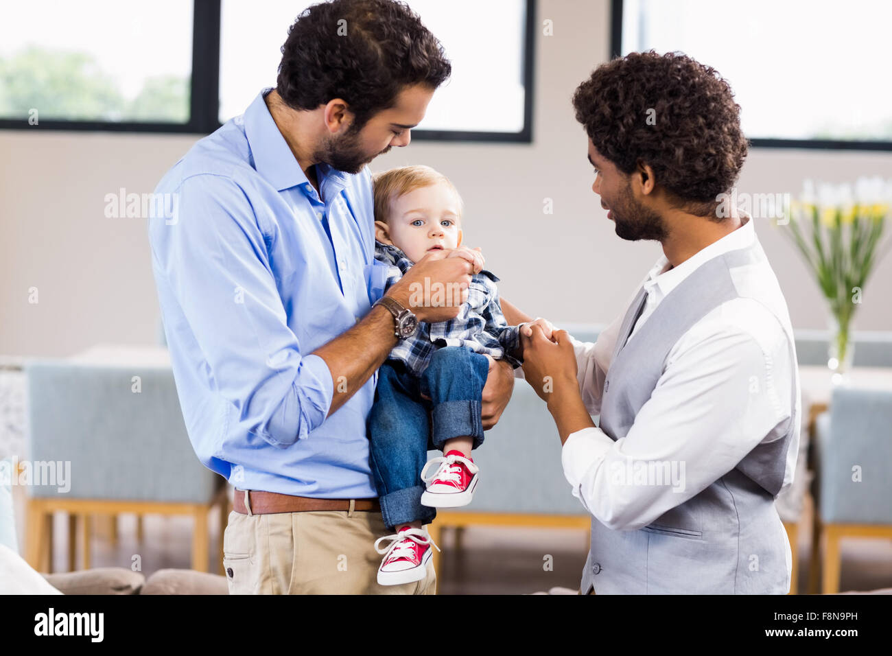 Happy gay couple with child - Stock Image