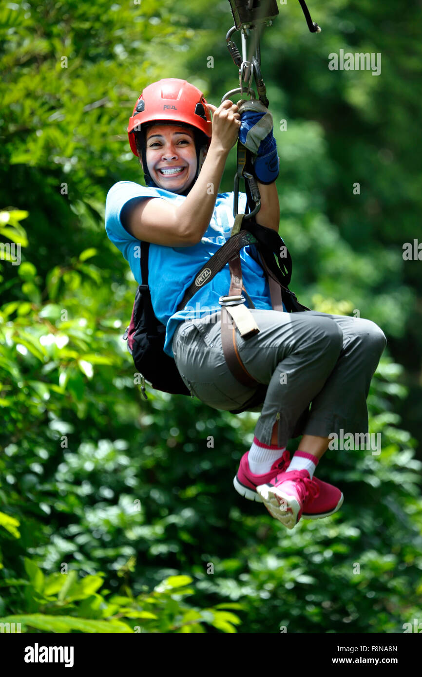 Woman on zip line, Ecoquest Adventures & Tours, Hacienda Campo Rico, Carolina, Puerto Rico - Stock Image