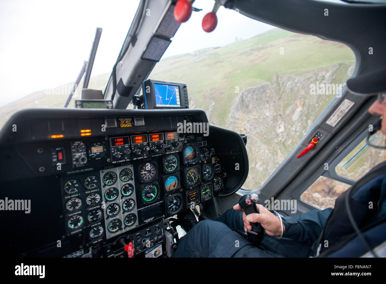 in the cockpit of a helicopter flying from the mainland to Lundy Island - te cliffs of Lundy through the window - Stock Image