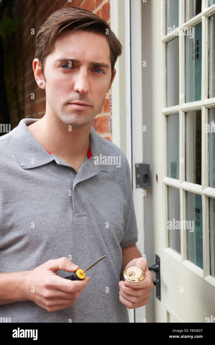Locksmith Fitting New Lock To Outside Door - Stock Image