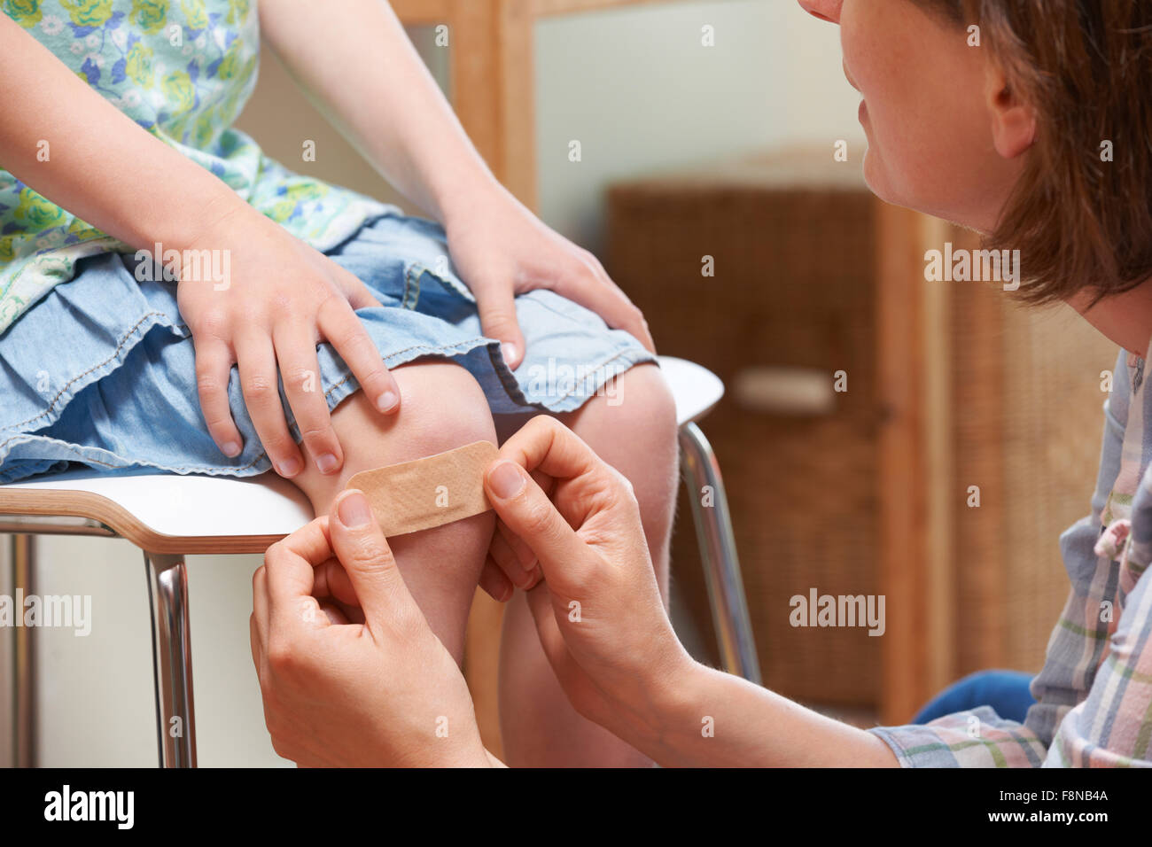 Mother Applying Adhesive Bandage To Daughter's Knee - Stock Image