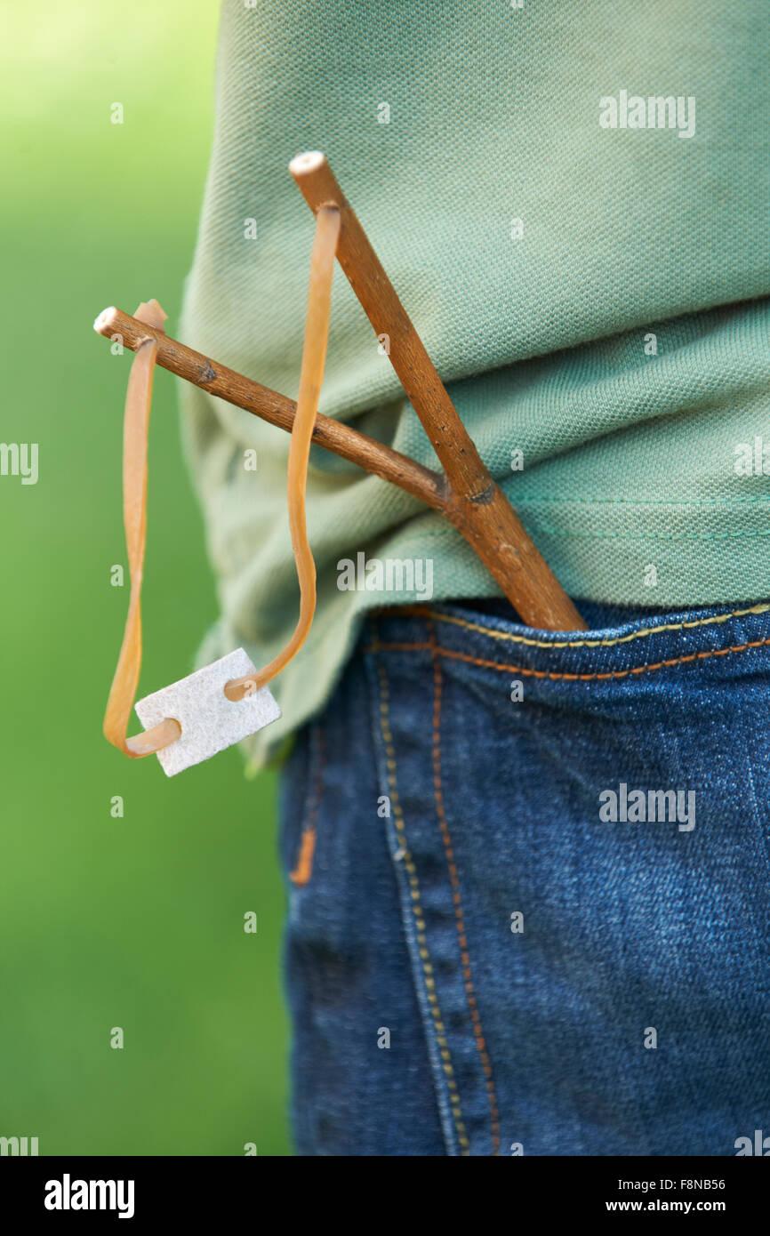 Close Up Of Slingshot In Boy's Trouser Pocket - Stock Image