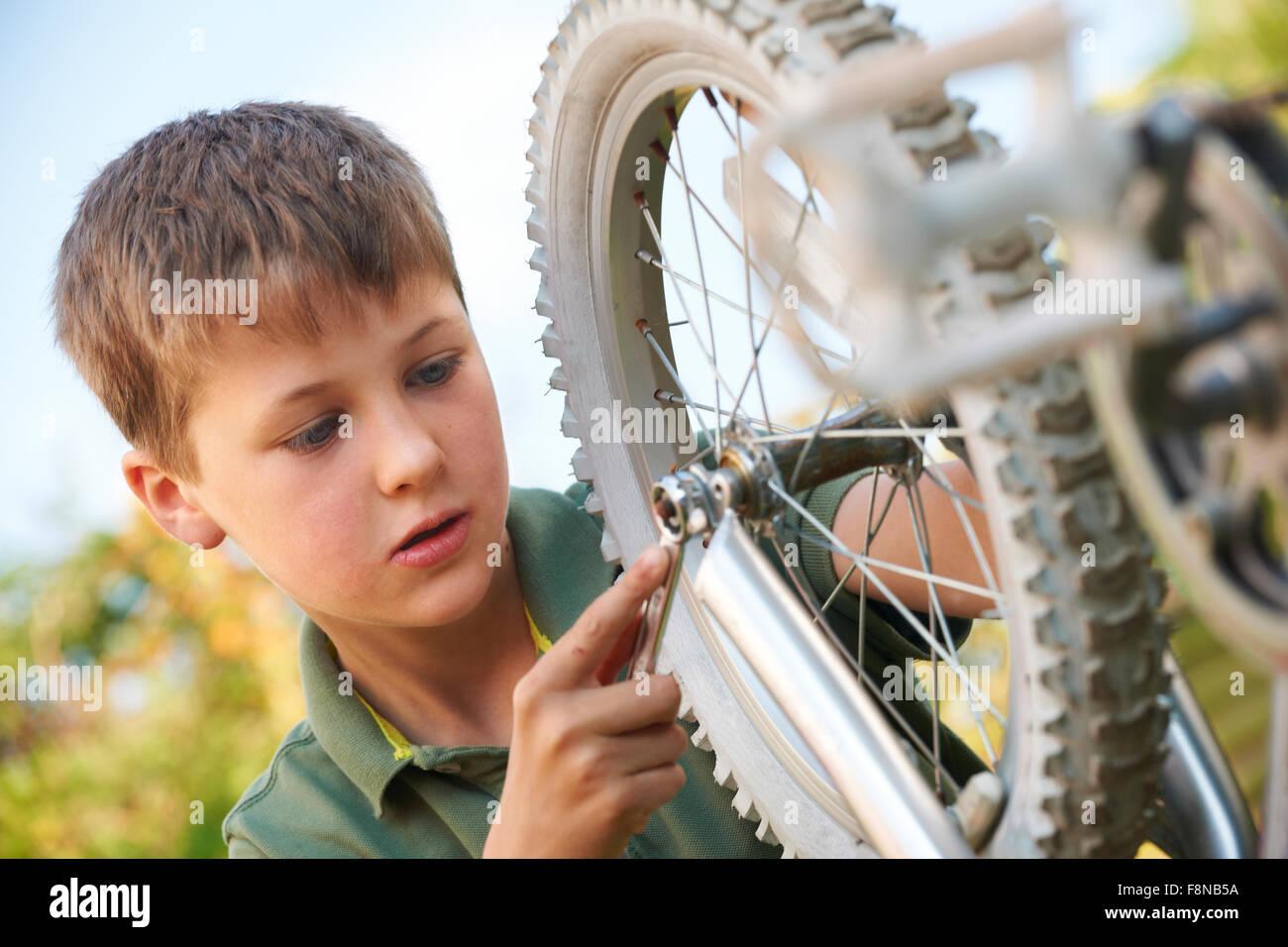 Boy Fixing Wheel Of Bike Stock Photo