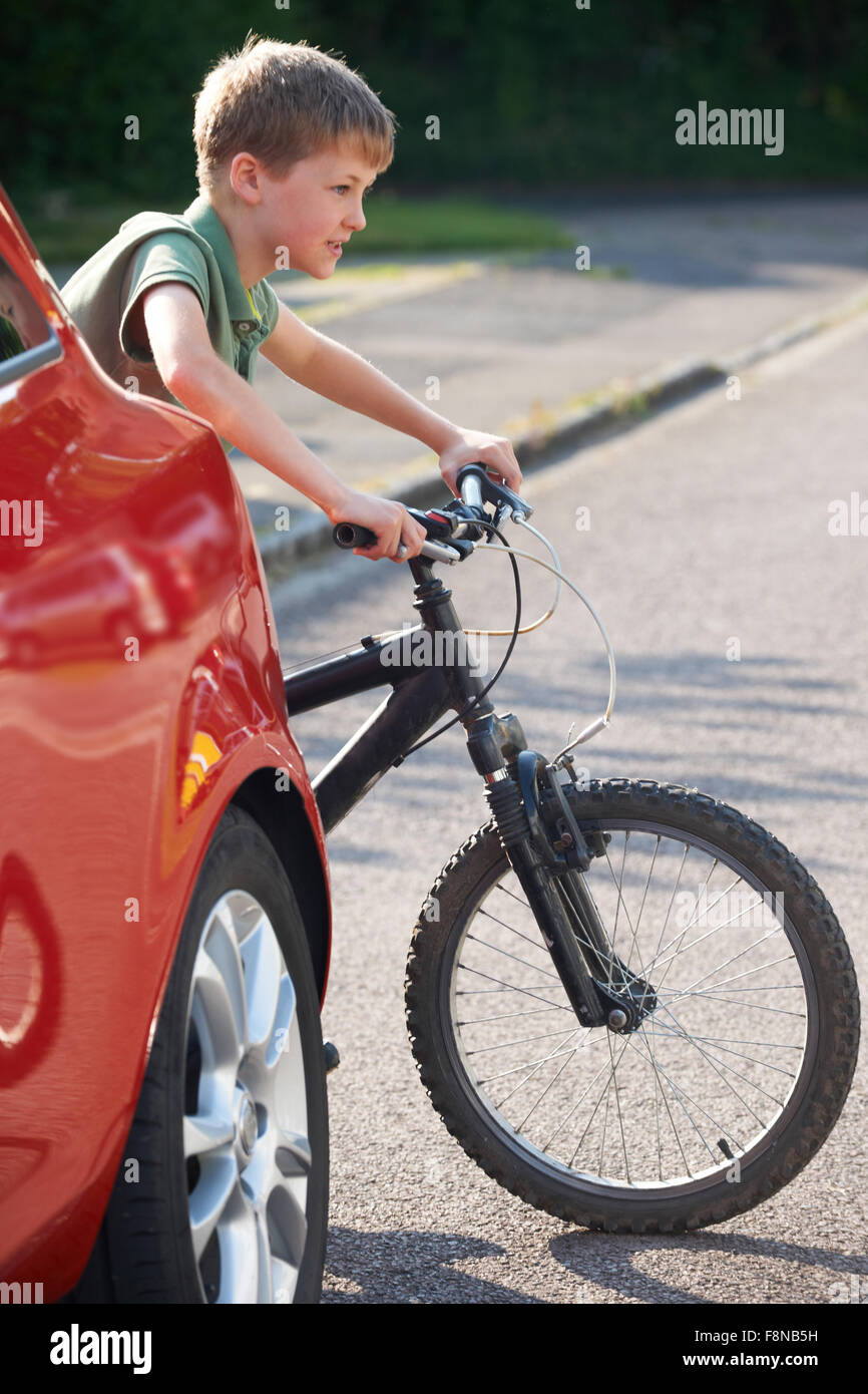 Child Riding Bike From Behind Parked Car - Stock Image