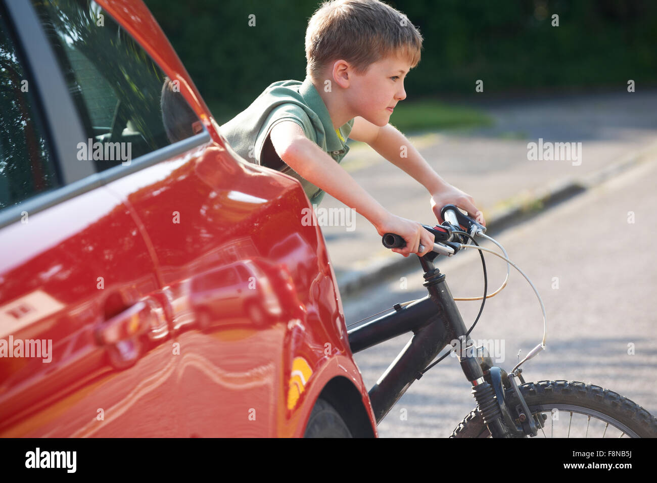 Child Riding Bike From Behind Parked Car Stock Photo