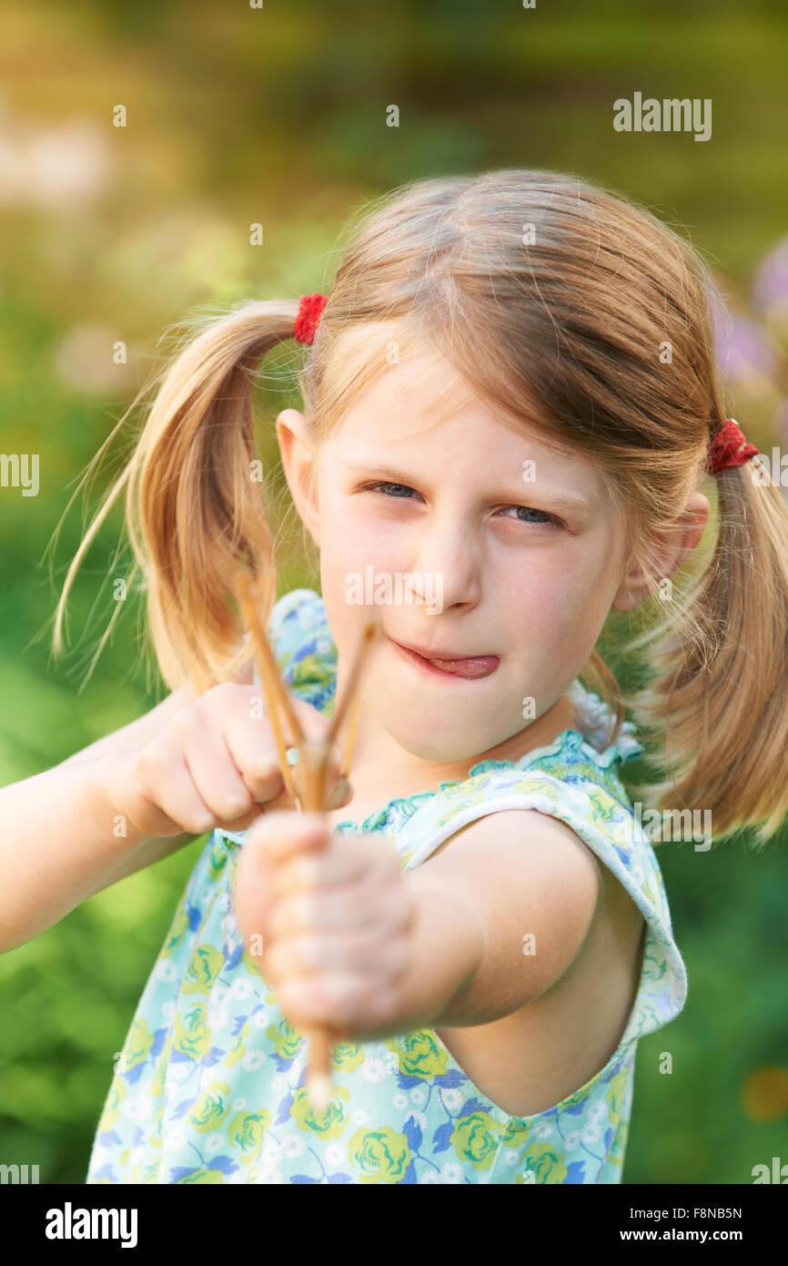 Girl Aiming Slingshot At Camera - Stock Image