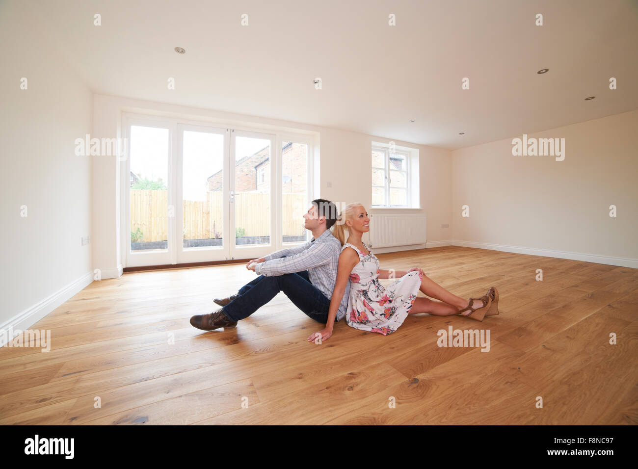 Young Couple Sitting In Empty Room Of Dream House - Stock Image