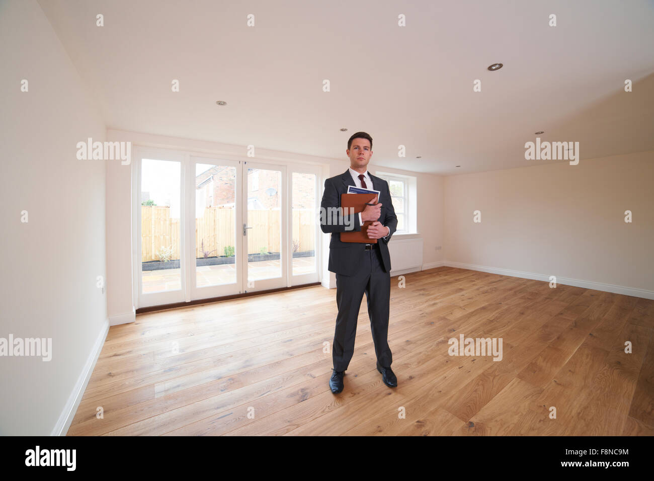 Estate Agent Looking At Vacant Property - Stock Image