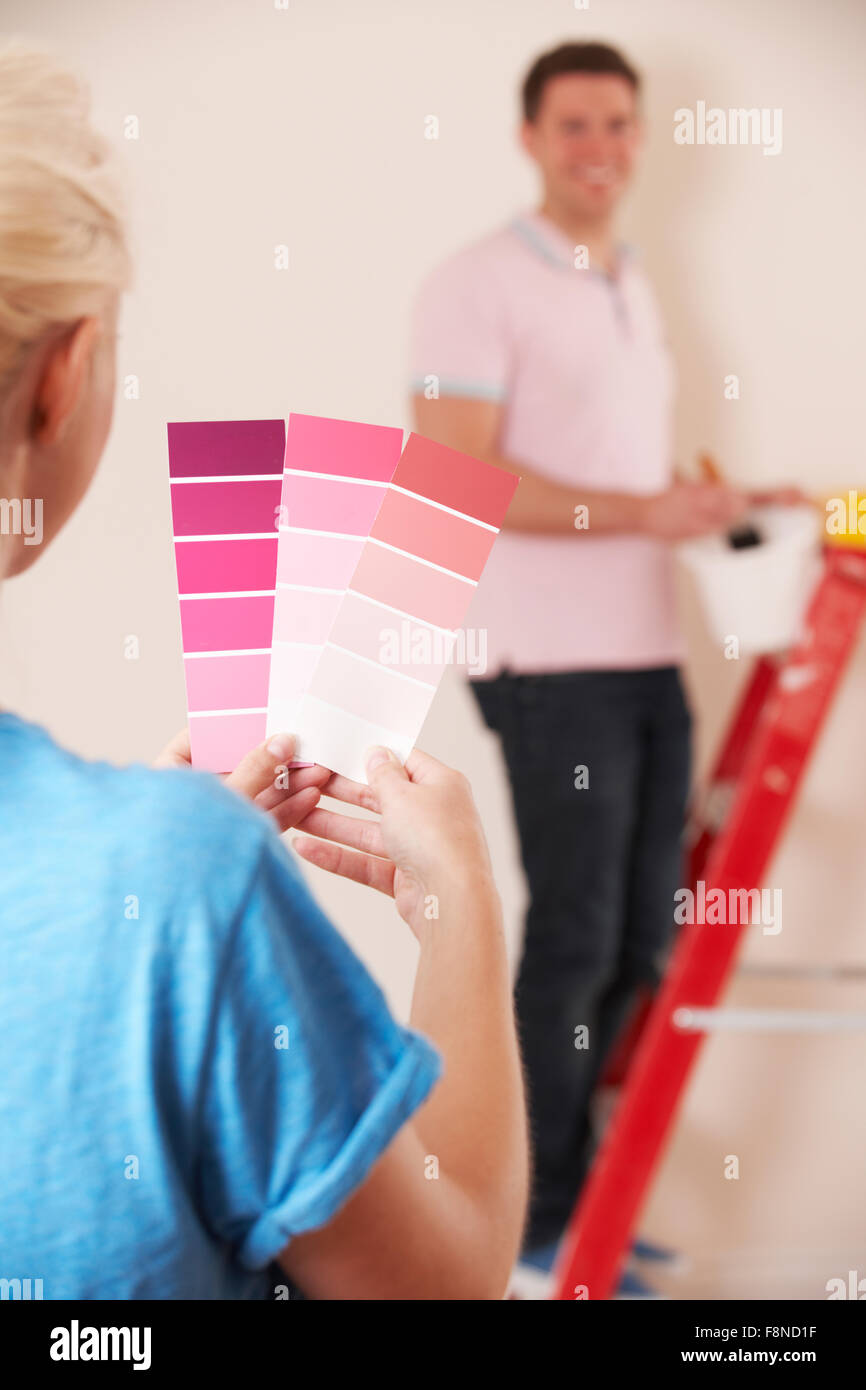 Young Couple Looking At Paint Swatches In New Home - Stock Image
