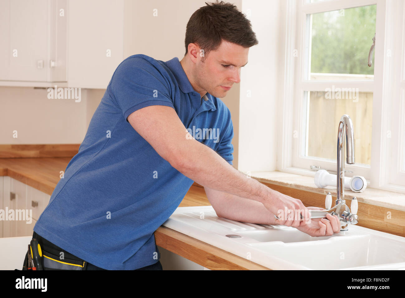 Plumber Mending Tap With Adjustable Wrench Stock Photo