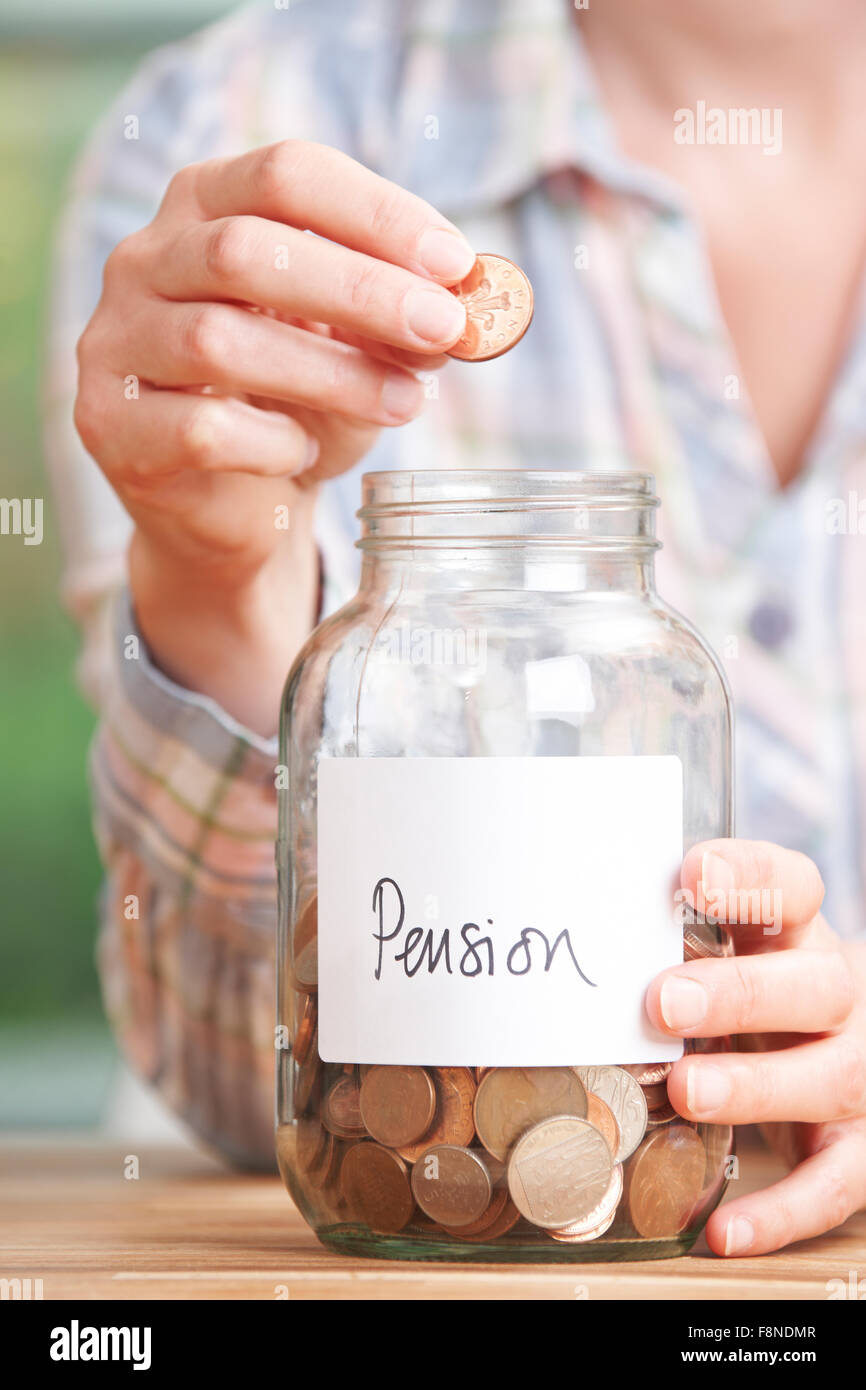 Woman Dropping Coins Into Jar Labelled Pension - Stock Image
