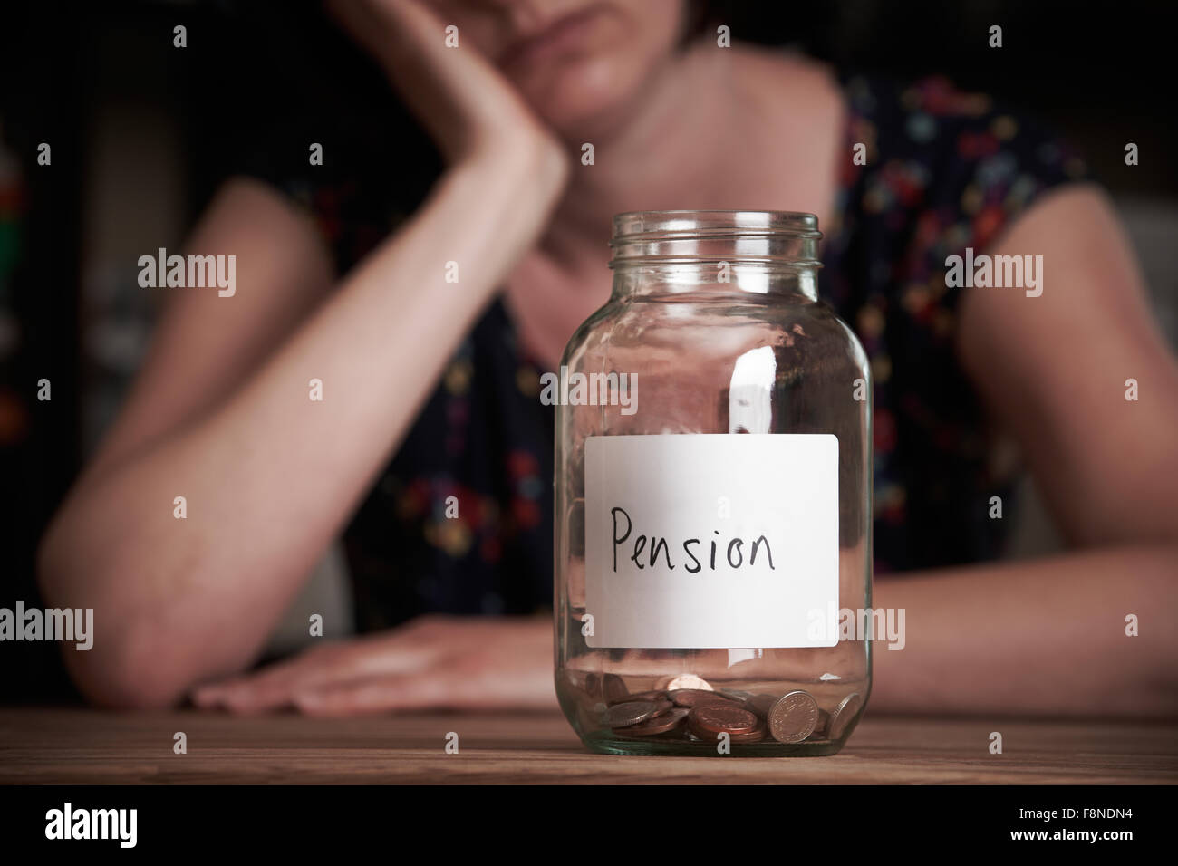 Depressed Woman Looking At Empty Jar Labelled Pension - Stock Image