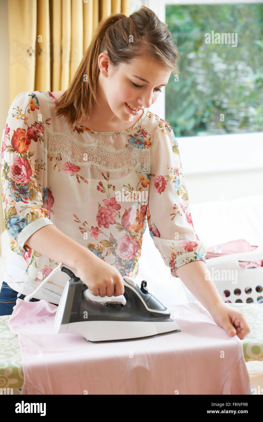 Teenager Girl Helping With Ironing At Home - Stock Image