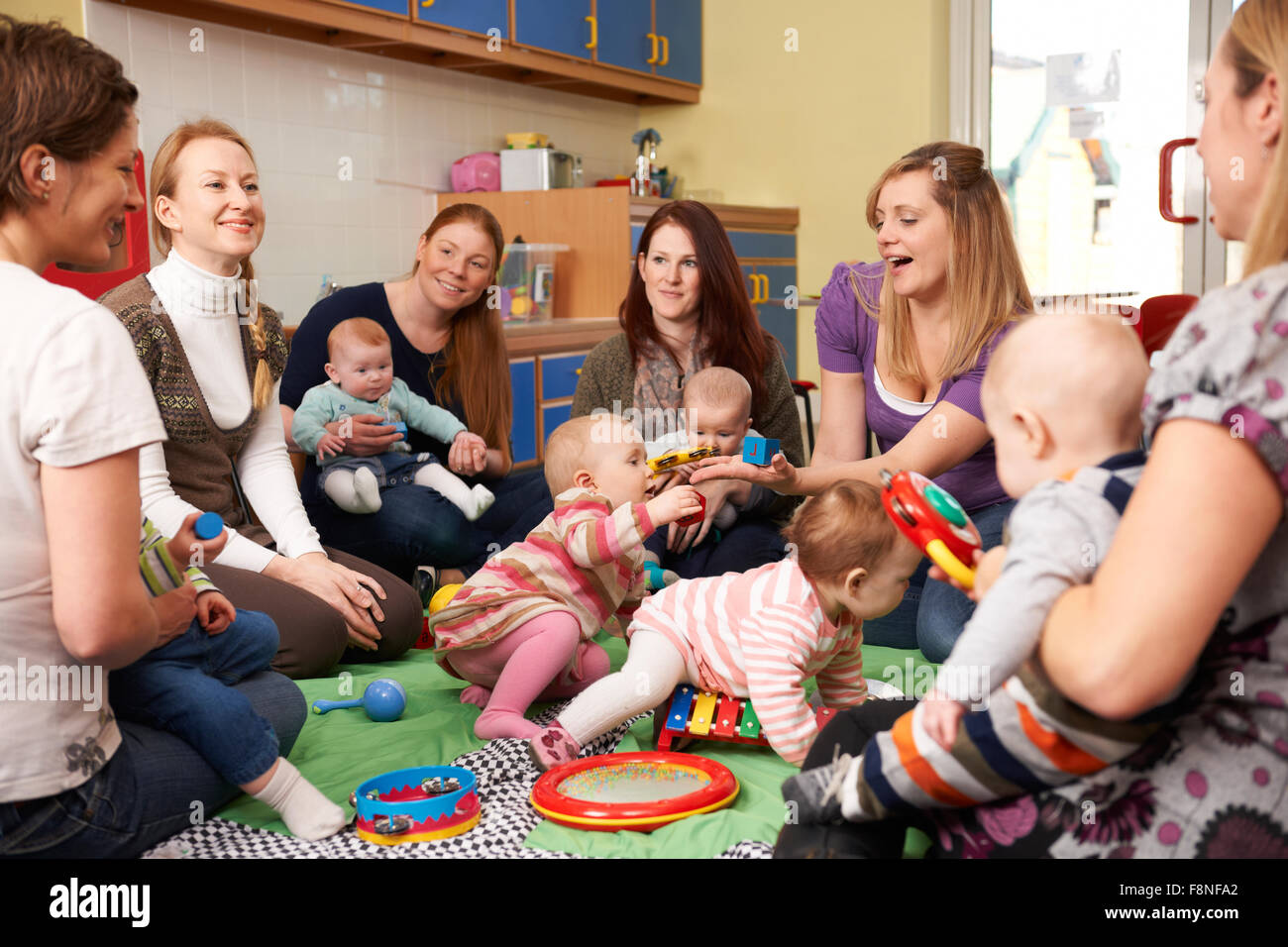 Group Of Mothers With Babies At Playgroup - Stock Image