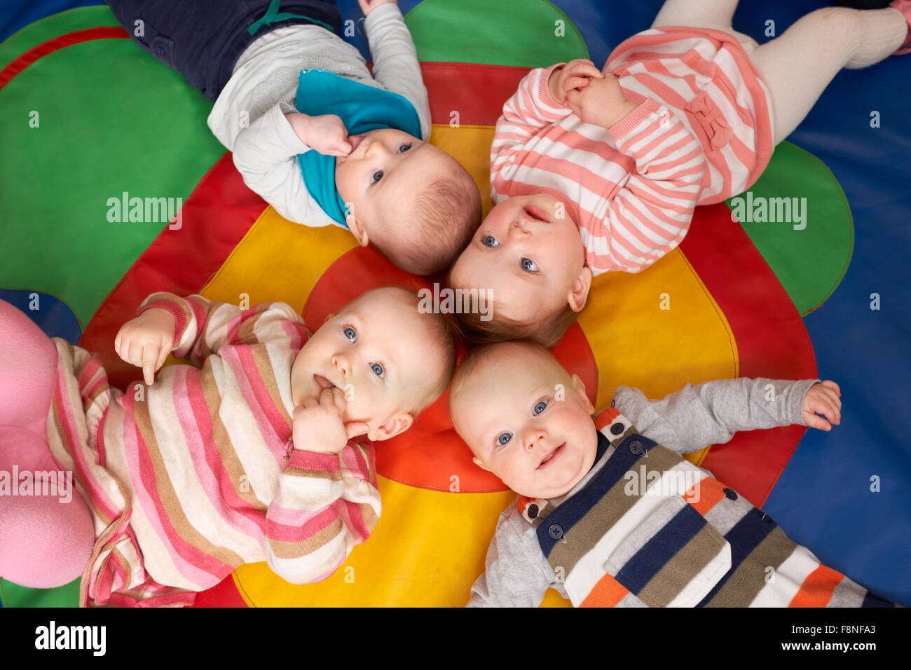 Overhead View Of Babies Lying On Mat At Playgroup - Stock Image