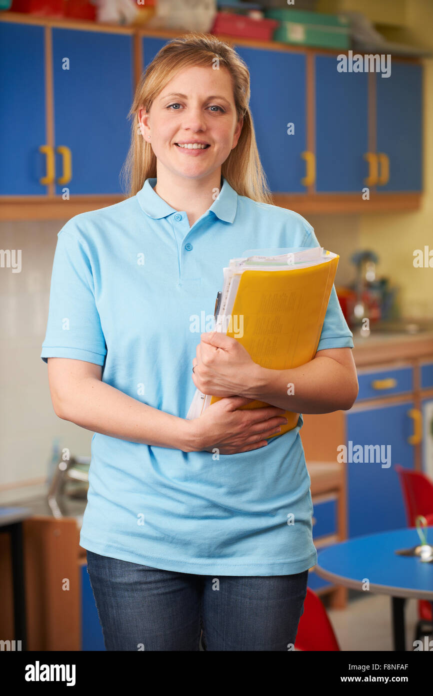 Childcare Worker Standing In Nursery - Stock Image