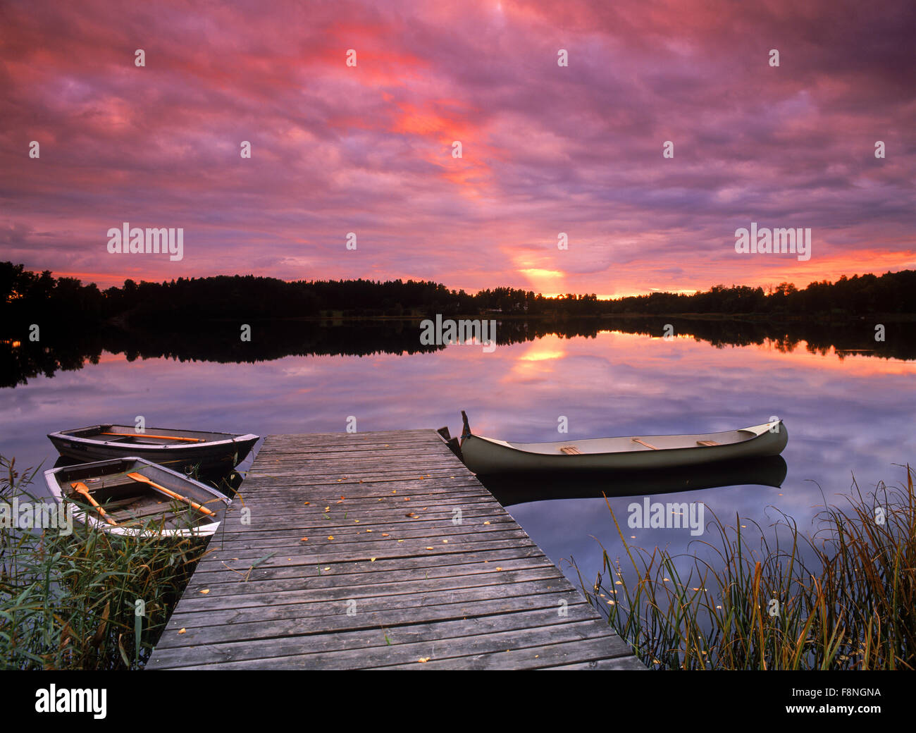 Canoe tied to lakeside dock at sunset in Sweden near town of Flen - Stock Image