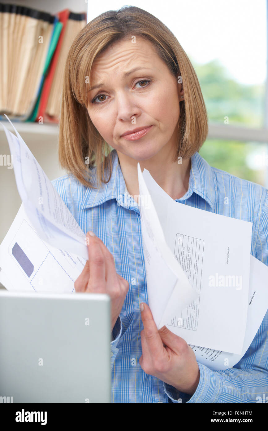 Woman Holding Bills Concerned About Debt - Stock Image
