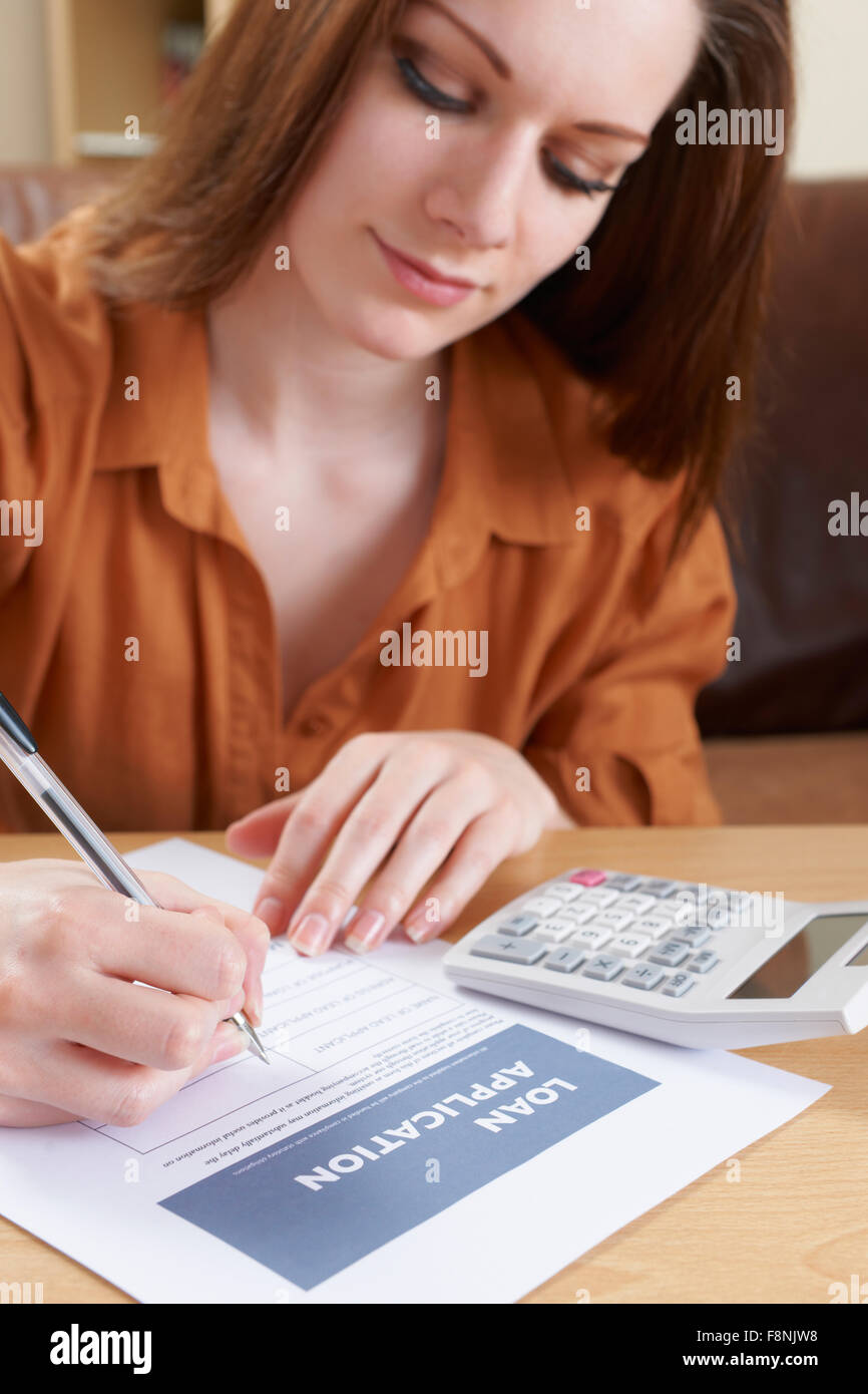Young Woman Completing Loan Application Form - Stock Image