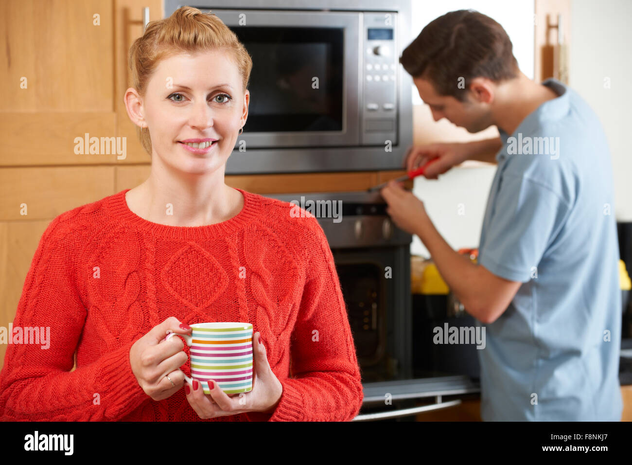Woman Smiling As Cooker Is Repaired - Stock Image