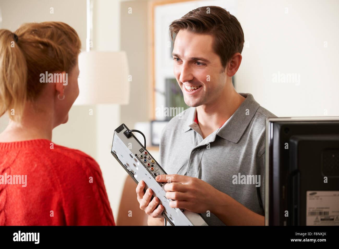 Engineer Giving Advice On Installing Digital TV Equipment - Stock Image