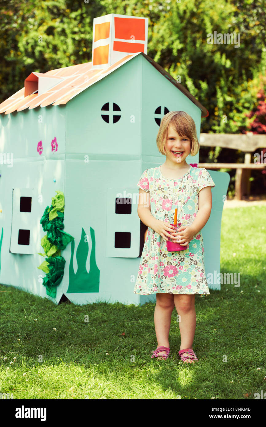 Young Girl Painting Cardboard Playhouse In Garden - Stock Image