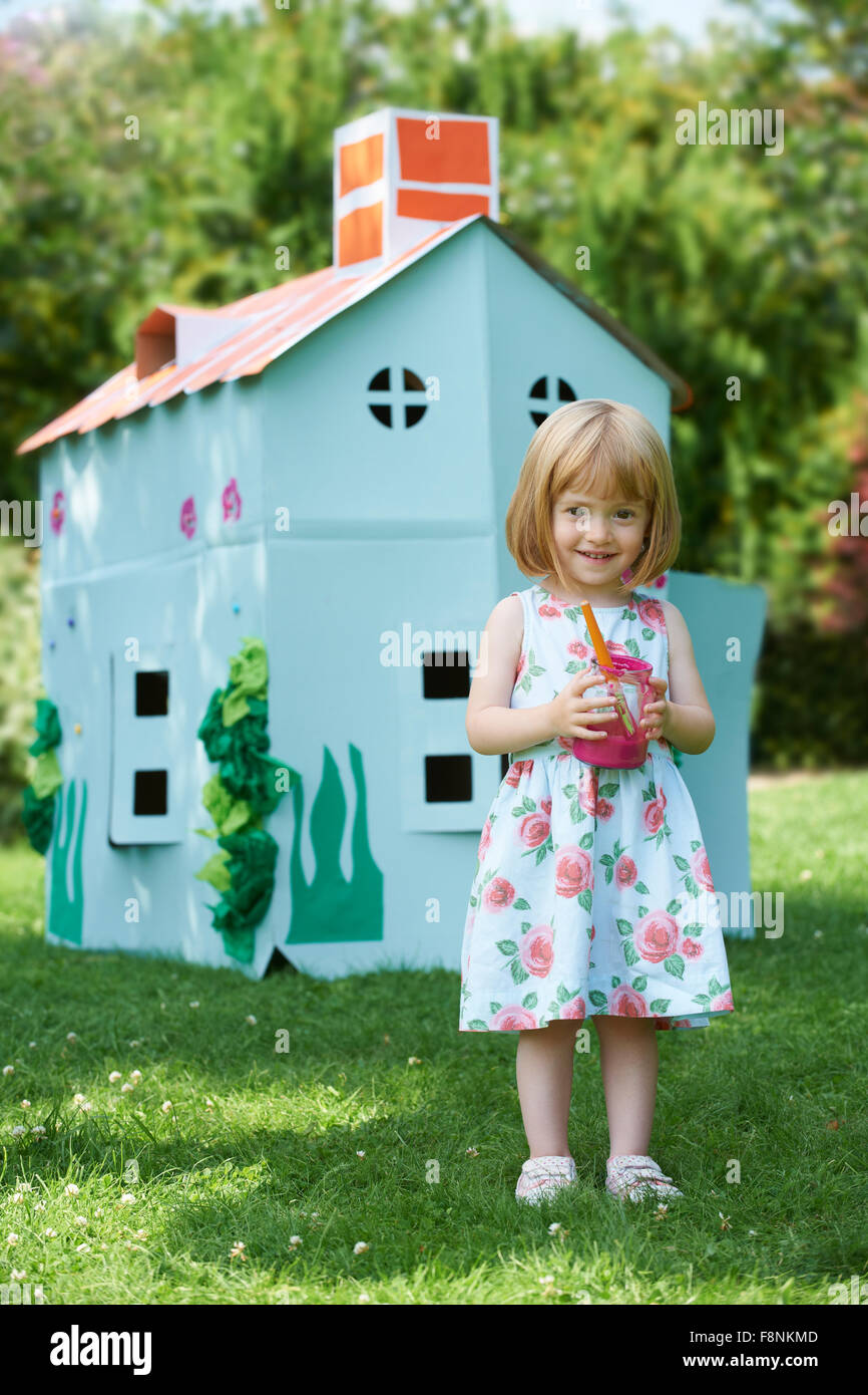 Young Girl Painting Home Made Cardboard House - Stock Image